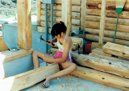 Jenn, 13, chiseling out holes for the electrical boxes in the logs for the house.